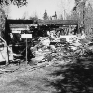 Kuvassa täysin tuhoutunut puusepänliike; mustuneita levyjä, katon ja seinänpalasia